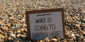 "A small white board sign on a shingle beach. The sign reads ""What is going to happen here?"""