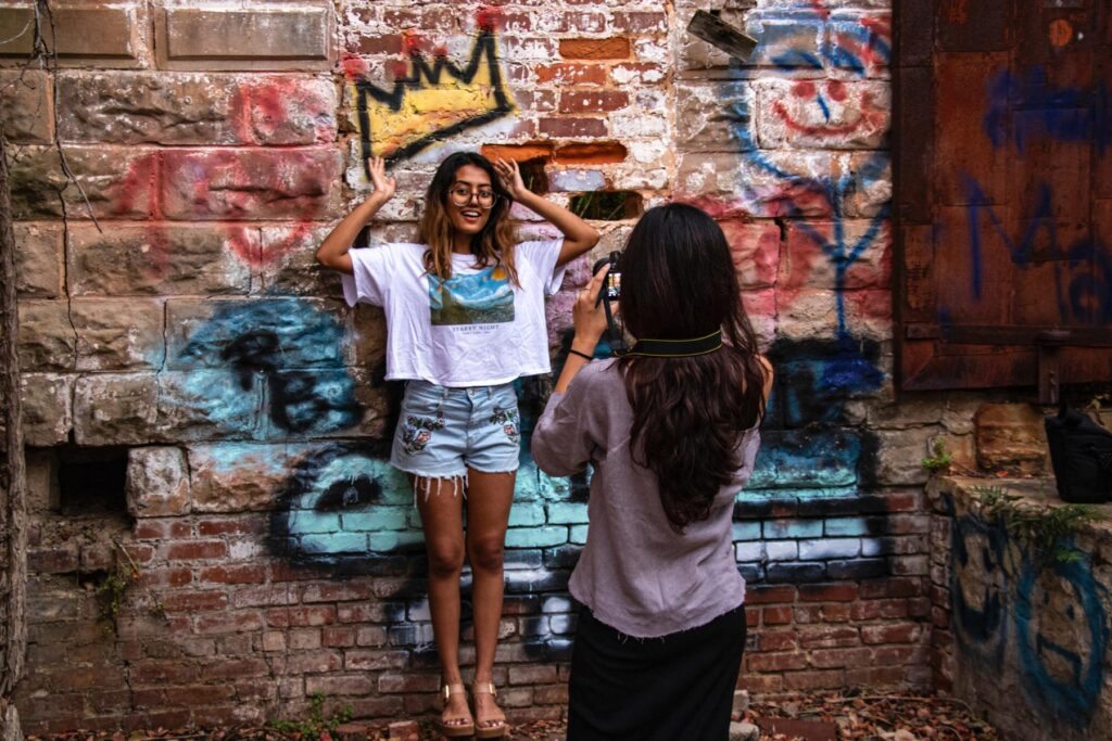 Photographing a fellow assembler in front of a brick wall with graffiti on it