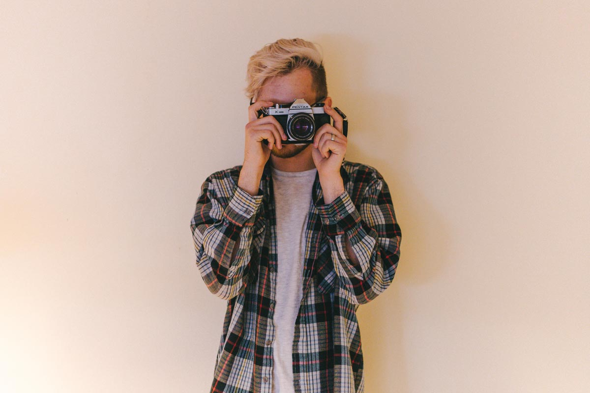 Young man taking a photo on a vintage camera